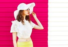 Mujer en el sombrero de paja blanco del verano que mira sobre rosa colorido Imagen de archivo libre de regalías