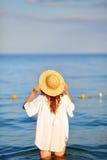 Mujer en el sombrero de paja que se coloca en agua de mar en la playa Foto de archivo