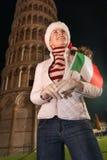 Mujer en el sombrero de Papá Noel con la bandera que mira para arriba cerca de la torre inclinada, Pisa Foto de archivo