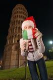 Mujer en el sombrero de Papá Noel con la torre inclinada cercana de la bandera italiana de Pisa Fotos de archivo libres de regalías