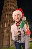 Mujer en el sombrero de Papá Noel con la torre inclinada cercana de la bandera italiana de Pisa Imagenes de archivo