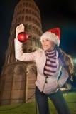 Mujer en el sombrero de Papá Noel con la torre inclinada cercana de la bola de la Navidad, Pisa Imagenes de archivo
