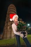 Mujer en el sombrero de Papá Noel con la torre inclinada cercana del árbol de navidad, Pisa Fotografía de archivo