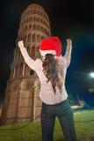 Mujer en el sombrero de Papá Noel que disfruta cerca de la torre inclinada de Pisa, Italia Imagenes de archivo