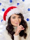 Mujer en el sombrero de Papá Noel que hace un gesto que hace callar Fotografía de archivo