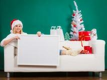 Mujer en el sombrero de Papá Noel que lleva a cabo al tablero en blanco blanco Imágenes de archivo libres de regalías