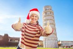 Mujer en el sombrero de Papá Noel que muestra los pulgares encima del viaje que se inclina cercano de Pisa Imagenes de archivo