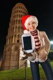 Mujer en el sombrero de Papá Noel que muestra a teléfono móvil la torre inclinada cercana, Pisa Foto de archivo libre de regalías
