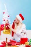 Mujer en el sombrero de Papá Noel que prepara los regalos de la Navidad Imagenes de archivo