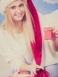 Mujer en el sombrero de Papá Noel que prepara los regalos de la Navidad Fotografía de archivo