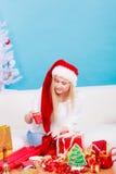 Mujer en el sombrero de Papá Noel que prepara los regalos de la Navidad Foto de archivo