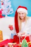 Mujer en el sombrero de Papá Noel que prepara los regalos de la Navidad Fotos de archivo libres de regalías