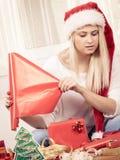 Mujer en el sombrero de Papá Noel que prepara los regalos de la Navidad Fotografía de archivo libre de regalías