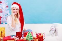 Mujer en el sombrero de Papá Noel que prepara los regalos de la Navidad Imágenes de archivo libres de regalías