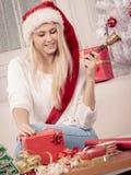 Mujer en el sombrero de Papá Noel que prepara los regalos de la Navidad Imagen de archivo