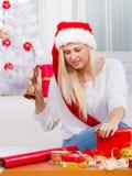 Mujer en el sombrero de Papá Noel que prepara los regalos de la Navidad Imagen de archivo libre de regalías