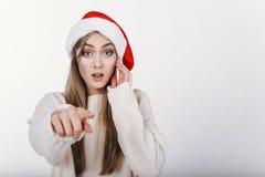 Mujer en el sombrero de Papá Noel que señala en la cámara por su finger Fotos de archivo libres de regalías