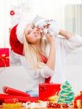 Mujer en el sombrero de Papá Noel que sostiene el regalo, decoración del muñeco de nieve Foto de archivo libre de regalías