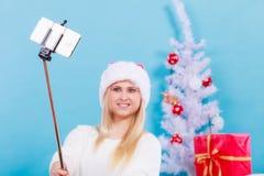 Mujer en el sombrero de Papá Noel que toma el selfie de la Navidad Imagenes de archivo