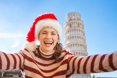 Mujer en el sombrero de Papá Noel que toma el selfie delante del viaje que se inclina, Pisa Foto de archivo