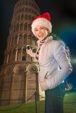 Mujer en el sombrero de Papá Noel que toma la foto de la torre inclinada de Pisa, Italia Foto de archivo