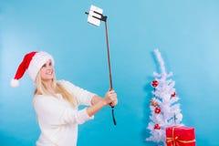 Mujer en el sombrero de Papá Noel que toma el selfie de la Navidad Imágenes de archivo libres de regalías