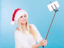 Mujer en el sombrero de Papá Noel que toma el selfie de la Navidad Imagen de archivo libre de regalías