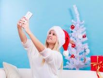Mujer en el sombrero de Papá Noel que toma el selfie de la Navidad Fotografía de archivo libre de regalías