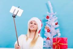 Mujer en el sombrero de Papá Noel que toma el selfie de la Navidad Fotos de archivo libres de regalías