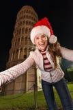 Mujer en el sombrero de Papá Noel que toma a selfie la torre inclinada cercana de Pisa Foto de archivo libre de regalías