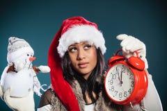 Mujer en el sombrero de santa con el pequeños muñeco de nieve y reloj Fotos de archivo libres de regalías