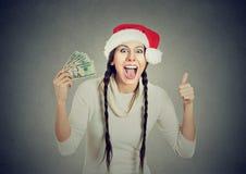 Mujer en el sombrero de santa con los billetes de dólar que muestran el pulgar para arriba foto de archivo libre de regalías