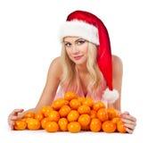 Mujer en el sombrero de santa con los mandarines Foto de archivo