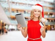 Mujer en el sombrero de santa con PC de la tableta y la tarjeta de crédito Imágenes de archivo libres de regalías