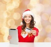 Mujer en el sombrero de santa con PC de la tableta y la tarjeta de crédito Imagen de archivo