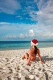 Mujer en el sombrero de santa en la playa Fotografía de archivo