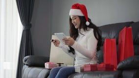 Mujer en el sombrero de santa que hace compras en línea para el regalo de la Navidad con la tableta digital en sala de estar