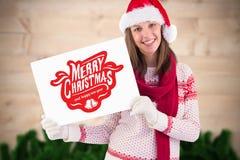 Mujer en el sombrero de santa que lleva a cabo un cartel de la Feliz Navidad Fotografía de archivo libre de regalías
