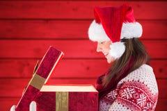 Mujer en el sombrero de santa que mira el regalo de la Navidad Foto de archivo libre de regalías