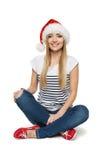 Mujer en el sombrero de Santa que se sienta en suelo Foto de archivo