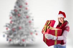 Mujer en el sombrero de santa que sostiene su caja de regalo grande de la Navidad Fotos de archivo libres de regalías