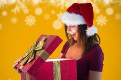 Mujer en el sombrero de santa sorprendida con su regalo de la Navidad Imagen de archivo
