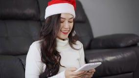 Mujer en el sombrero de santa usando la tableta digital en sala de estar