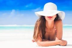 Mujer en el sombrero del bikini y de paja que miente en la playa tropical imagenes de archivo