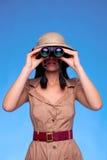 Mujer en el sombrero del safari que mira a través de los prismáticos imágenes de archivo libres de regalías