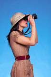 Mujer en el sombrero del safari que mira a través de los prismáticos Sid foto de archivo libre de regalías