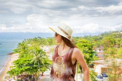Mujer en el sombrero que mira el horizonte, la playa y los árboles foto de archivo libre de regalías