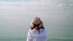 Mujer en el sombrero que mira el mar almacen de video