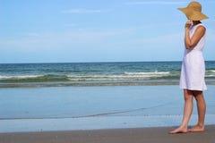 Mujer en el sombrero que se coloca en la playa que mira el océano Imágenes de archivo libres de regalías