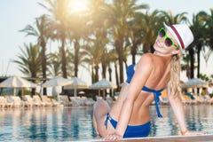 Mujer en el sombrero que se relaja en la piscina Muchacha en la piscina del balneario del viaje Vacaciones del lujo del verano imagenes de archivo